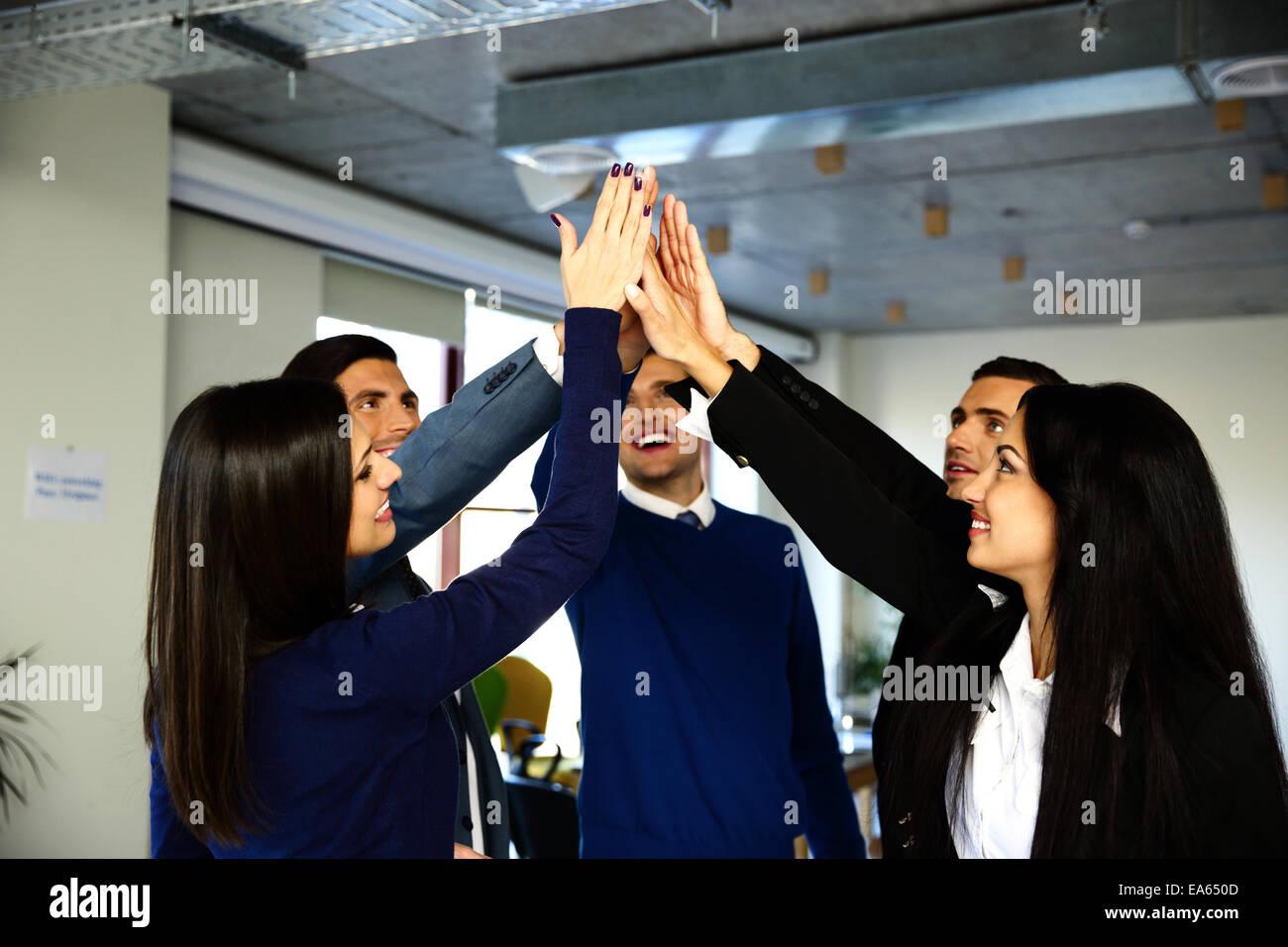 Feliz equipo empresarial es la celebración de manos juntas. Elevando una mano hacia arriba Imagen De Stock