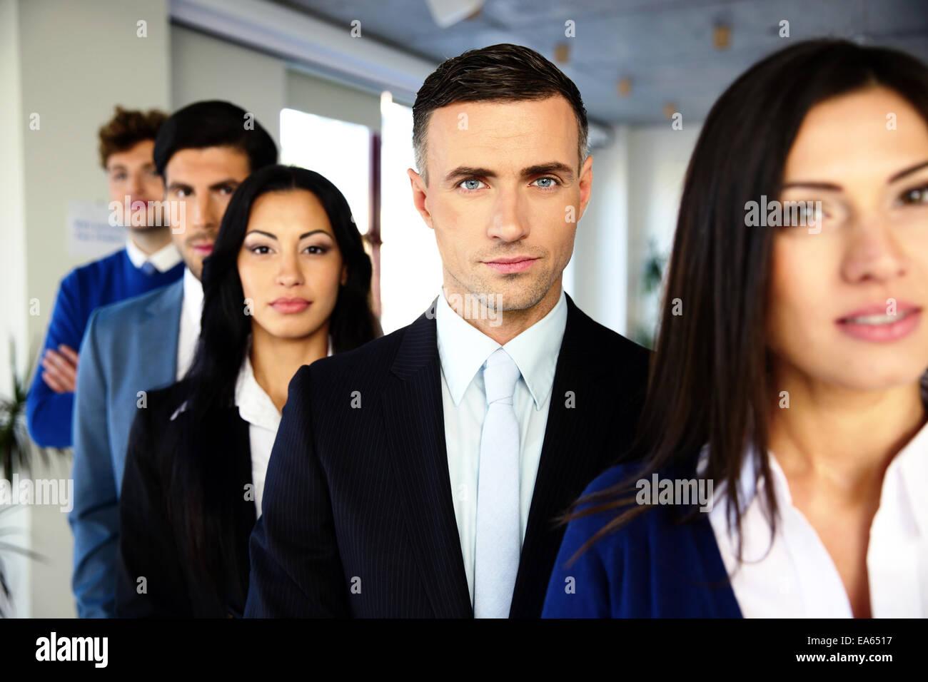 Grupo de un negocio serio, gente de pie en una fila en la oficina Imagen De Stock