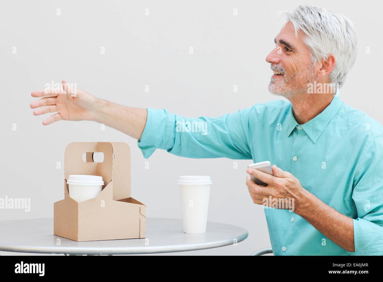 El empresario en la cafetería al aire libre saludo alguien Foto de stock