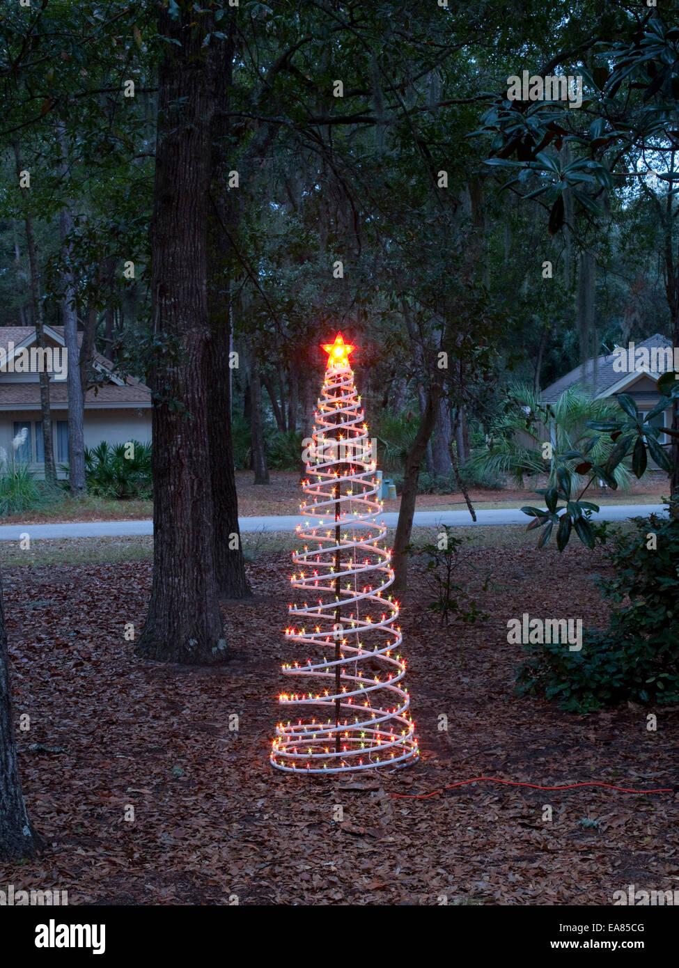 Árbol de navidad artificial en el crepúsculo del patio suburbano Foto de stock