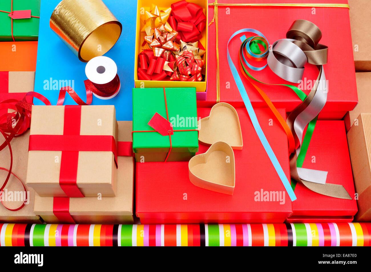 Un montón de diferentes cajas, papel de envolver, cintas y lazos de cinta de diferentes colores para preparar Imagen De Stock