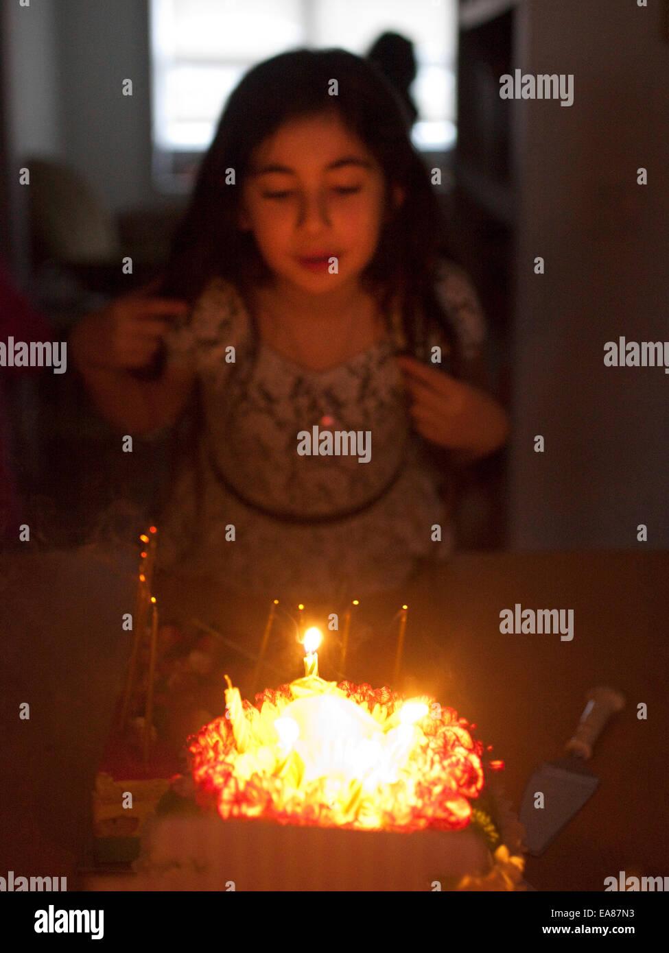Niña en casa soplar las velas en una tarta de cumpleaños. Imagen De Stock