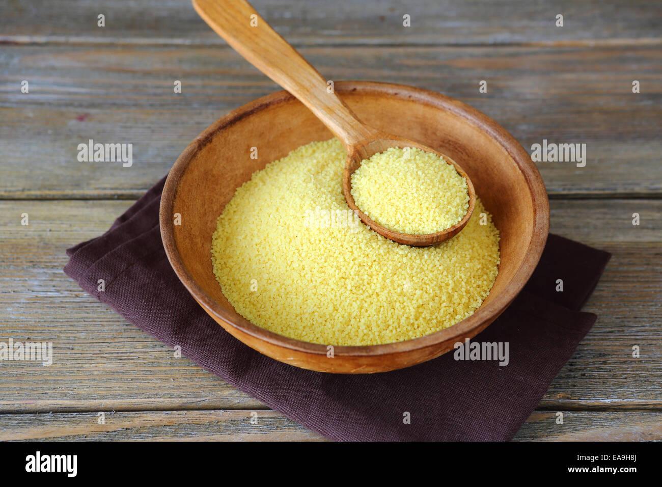 Cuscús árabe en un tazón sobre tablas de madera, ingrediente alimentario Imagen De Stock