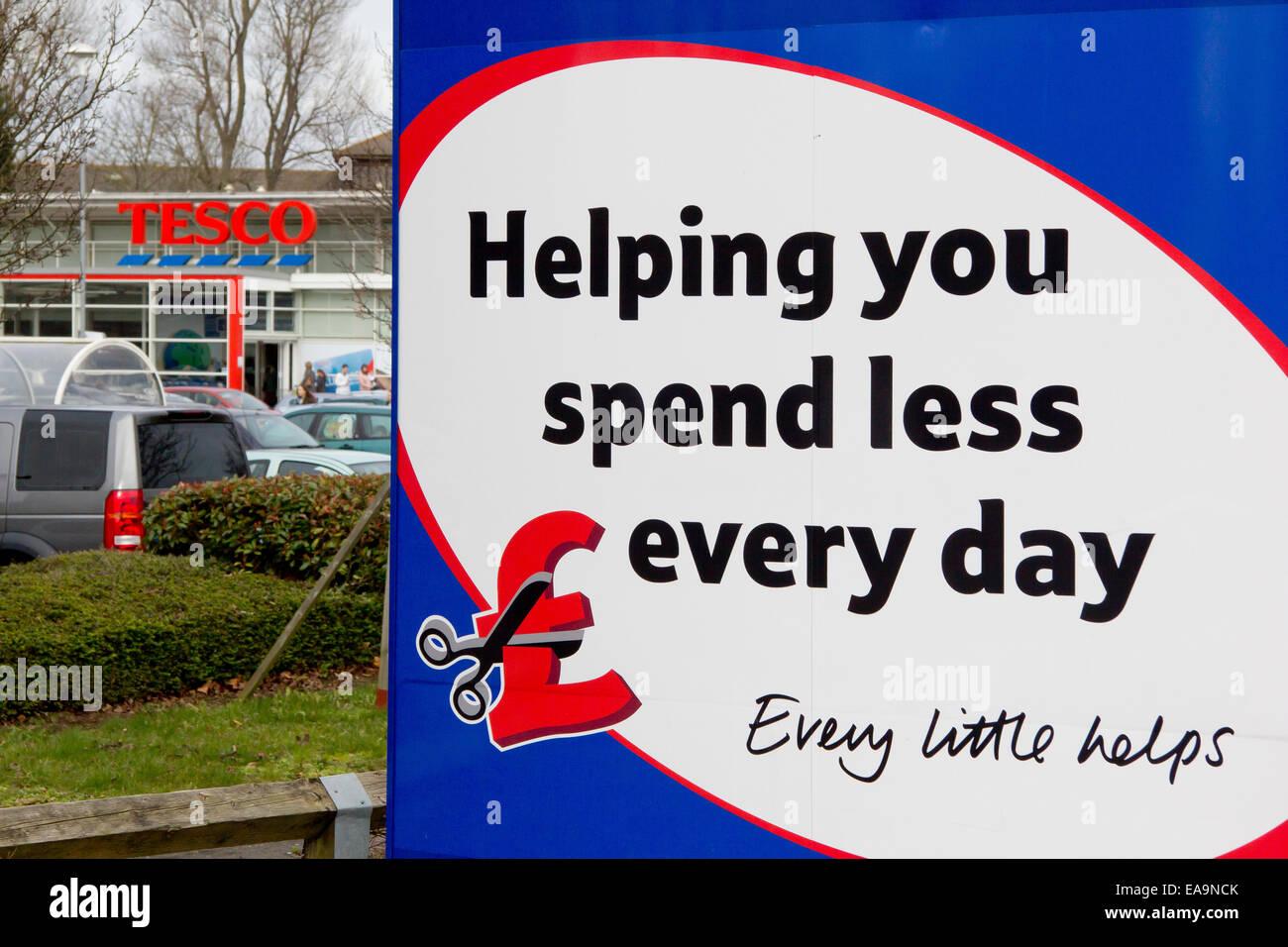 Tienda Tesco y slogan publicitario, ayudándole a gastar menos cada día, Taunton, Somerset. Tesco plc es Imagen De Stock