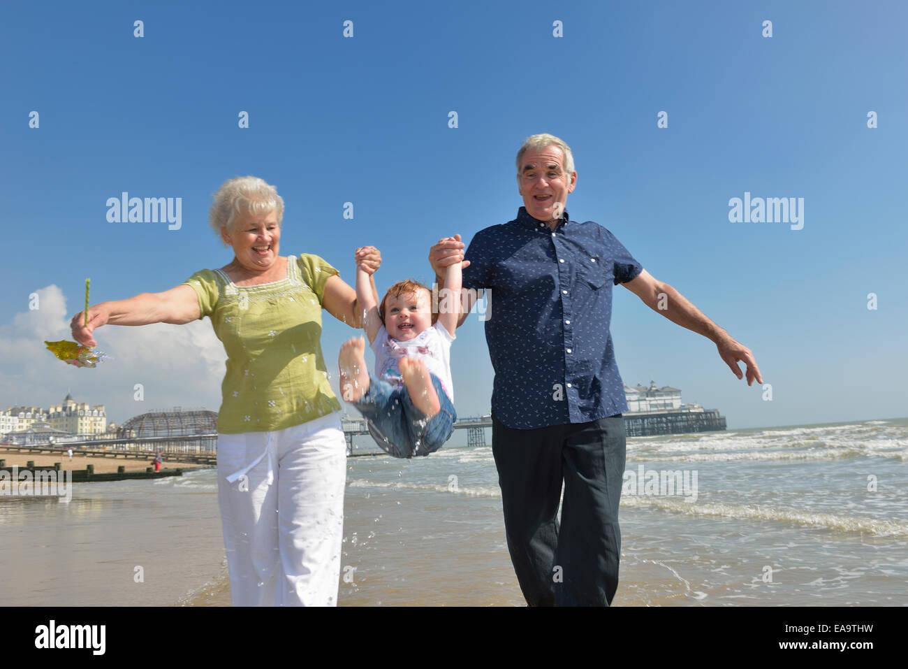 Los abuelos tomados de la mano y moviendo su nieta en la playa de Eastbourne. East Sussex. UK Imagen De Stock
