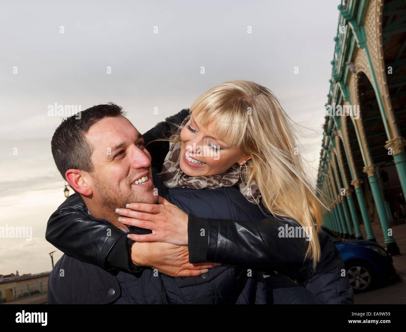 Un par disfrutar de un día en el mar británico en Brighton en ropa de abrigo de invierno Imagen De Stock