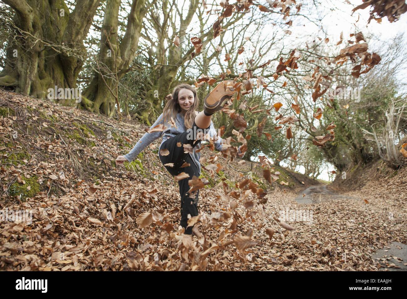 Chica jugando en hojarasca, darles patadas en el aire. Foto de stock