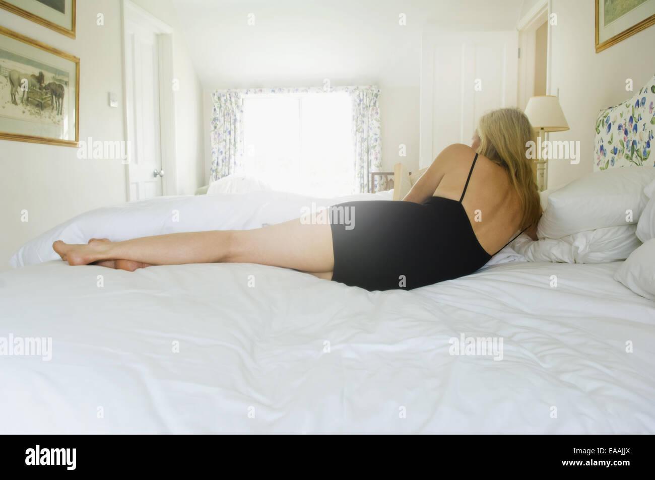 Un rubio mujer acostada de lado en una cama. Imagen De Stock