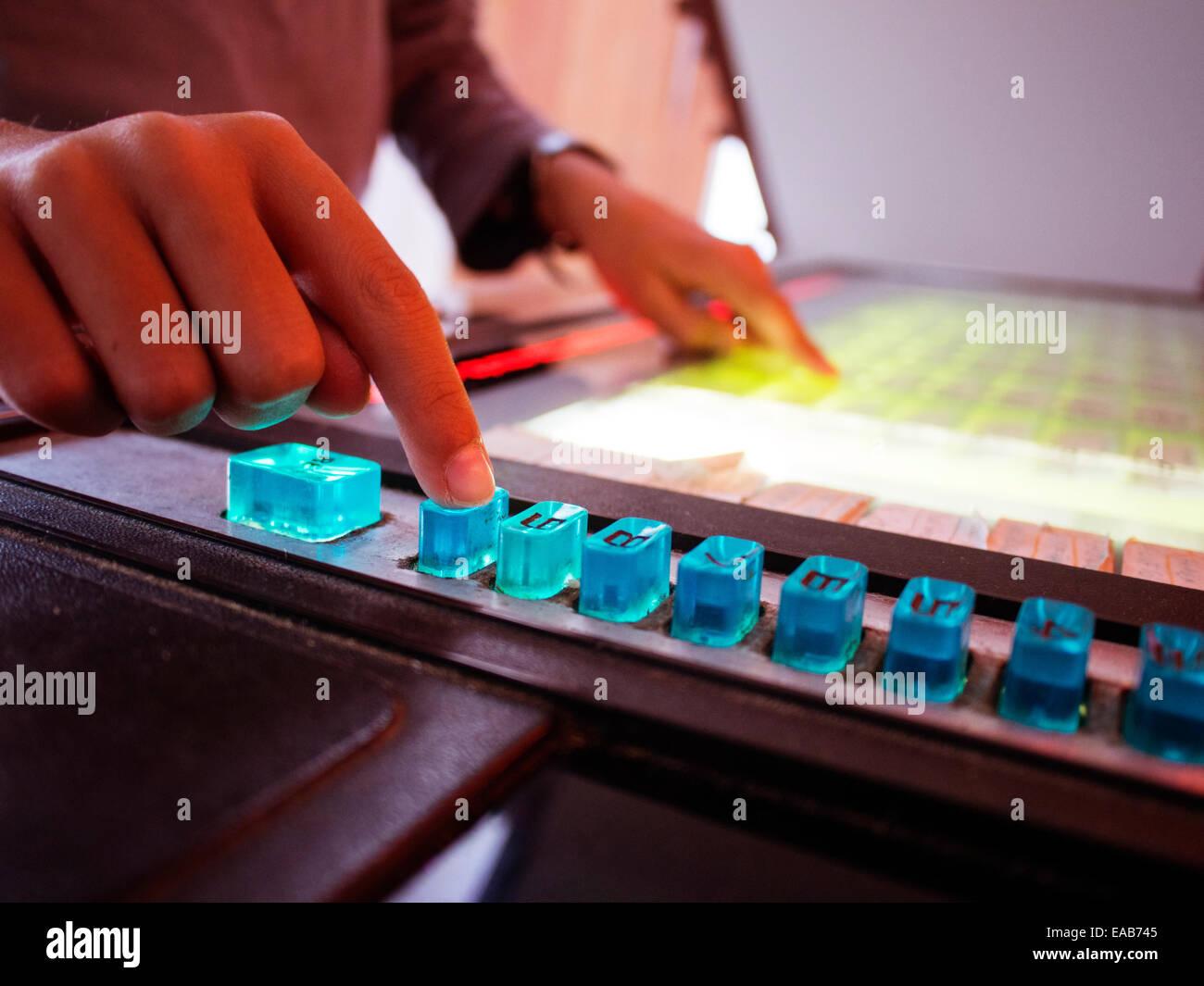 Boy selecciona canciones en botón juke box Foto de stock