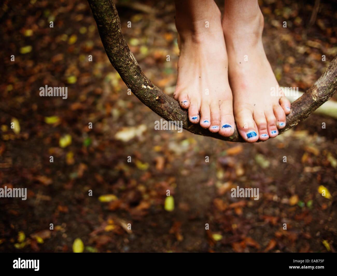 Chica destaca sobre vid columpio colgando de los árboles en el bosque Foto de stock