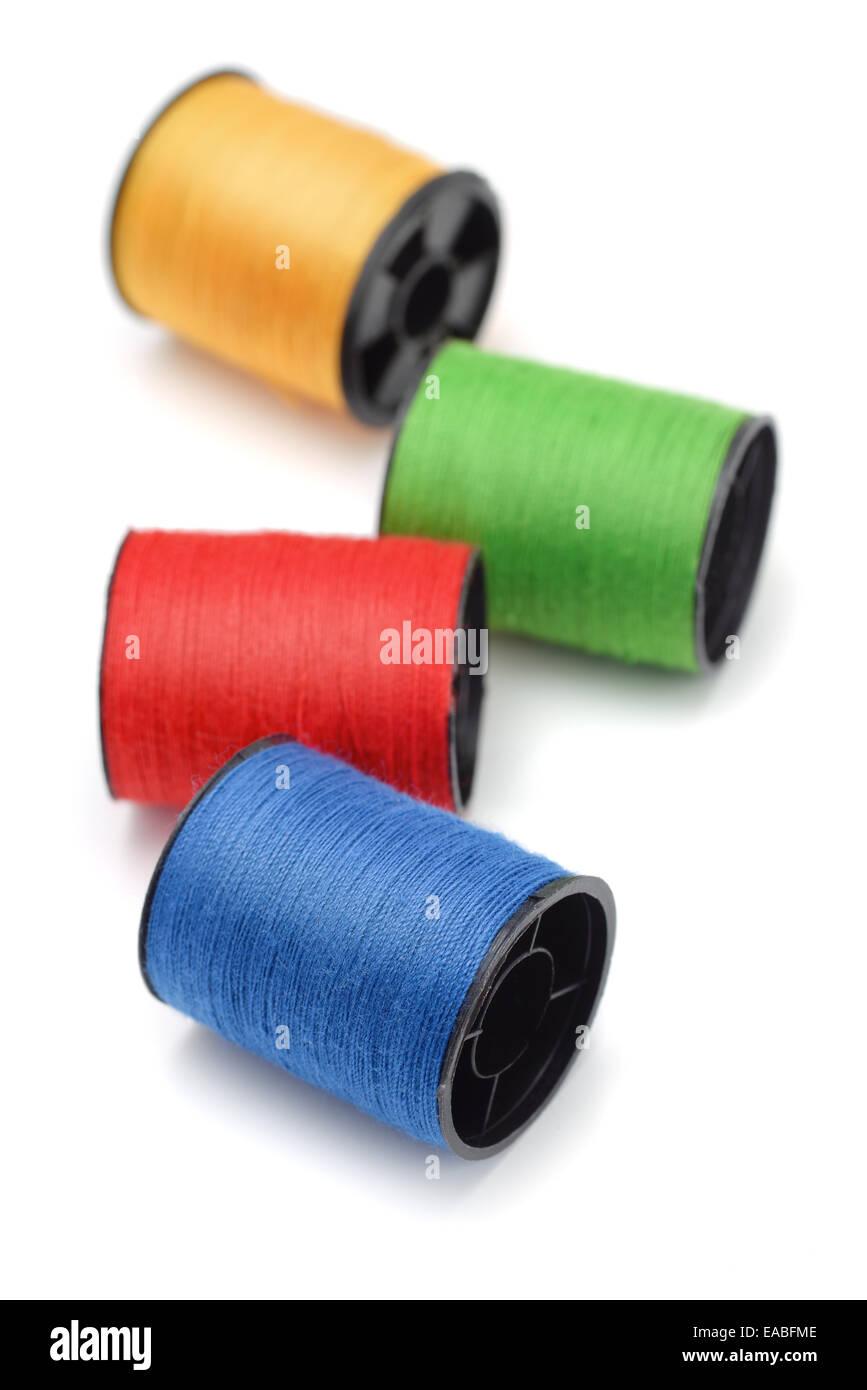 Cuatro bobinas de hilo de color aislado en blanco Foto de stock