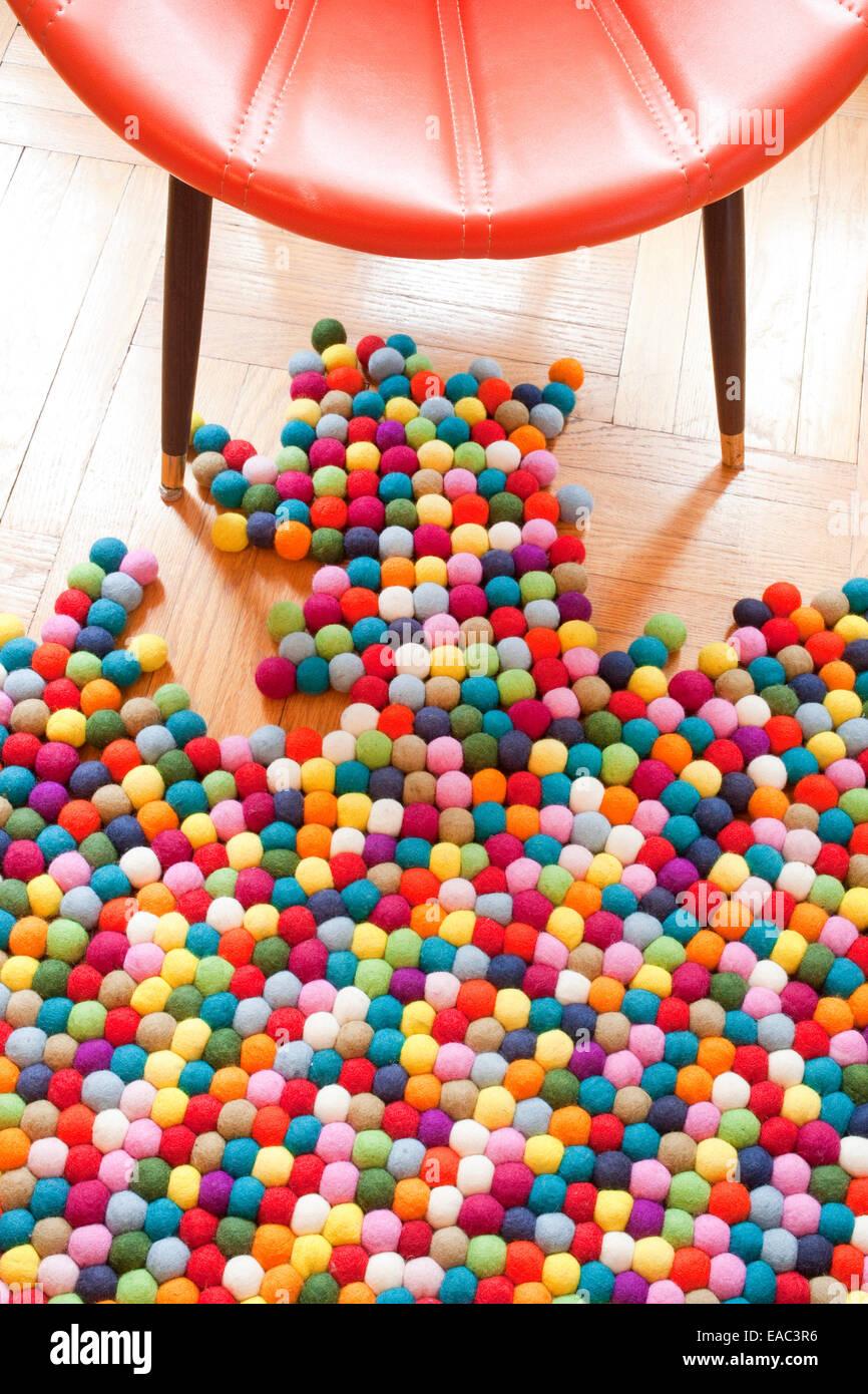 Alfombra colorida y una silla en un piso de madera Imagen De Stock
