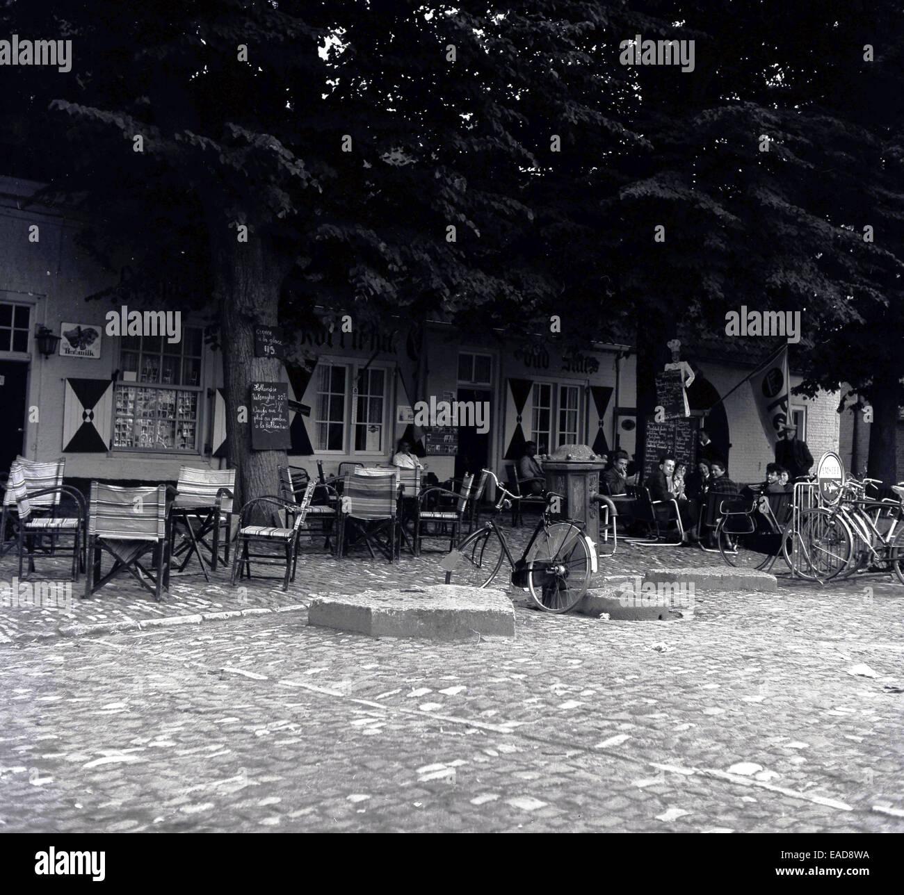 1950 foto histórica de bicicletas estacionados fuera una cafetería, Bélgica. Imagen De Stock