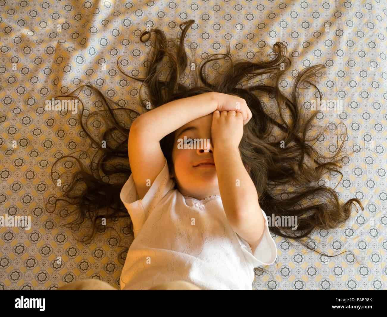 Joven con un montón de pelo de poner una cara graciosa mientras está acostada en la cama Imagen De Stock