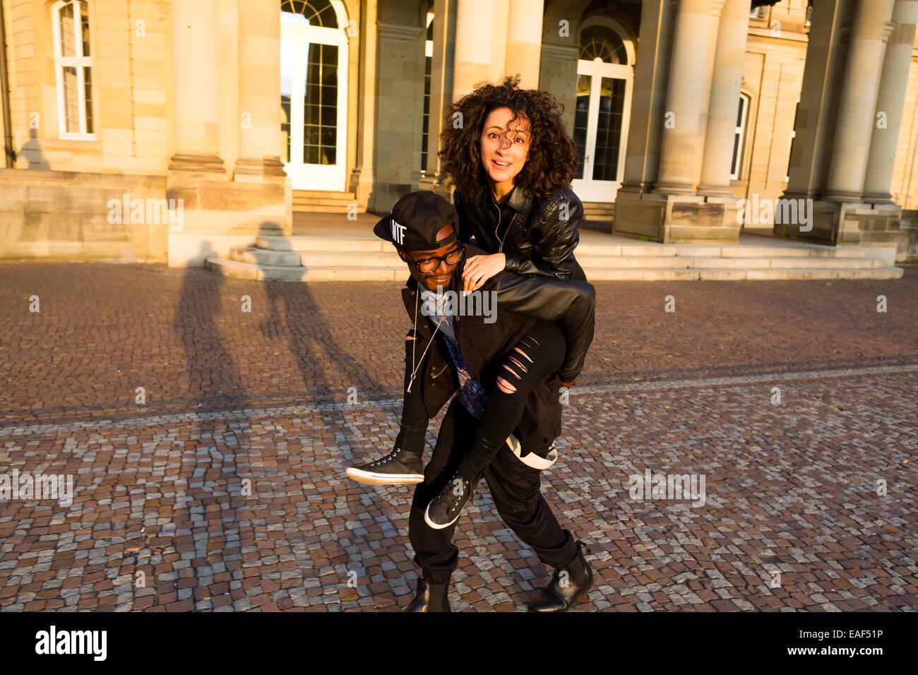 El hombre lleva una mujer afroamericana piggyback Foto de stock
