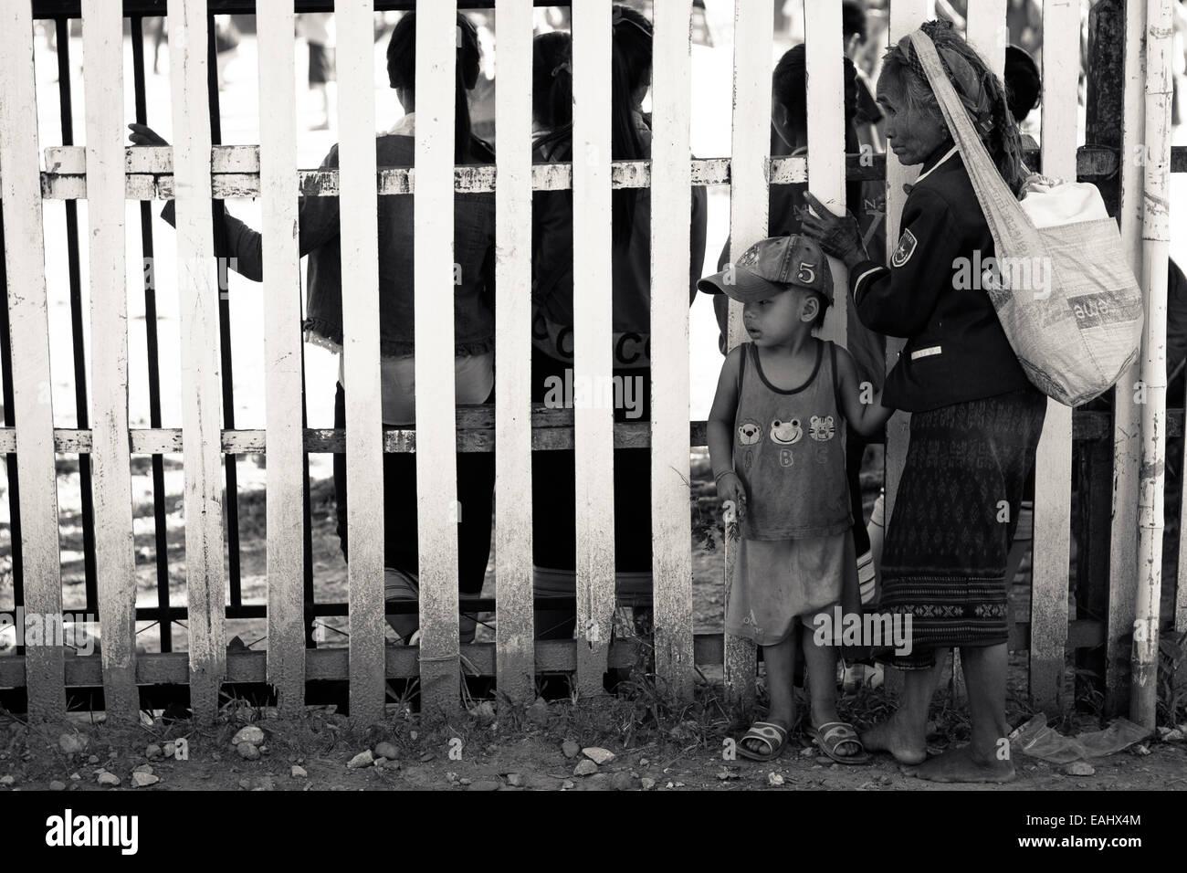 Una abuela y su nieto Lao viendo un rendimiento a través de una valla Imagen De Stock