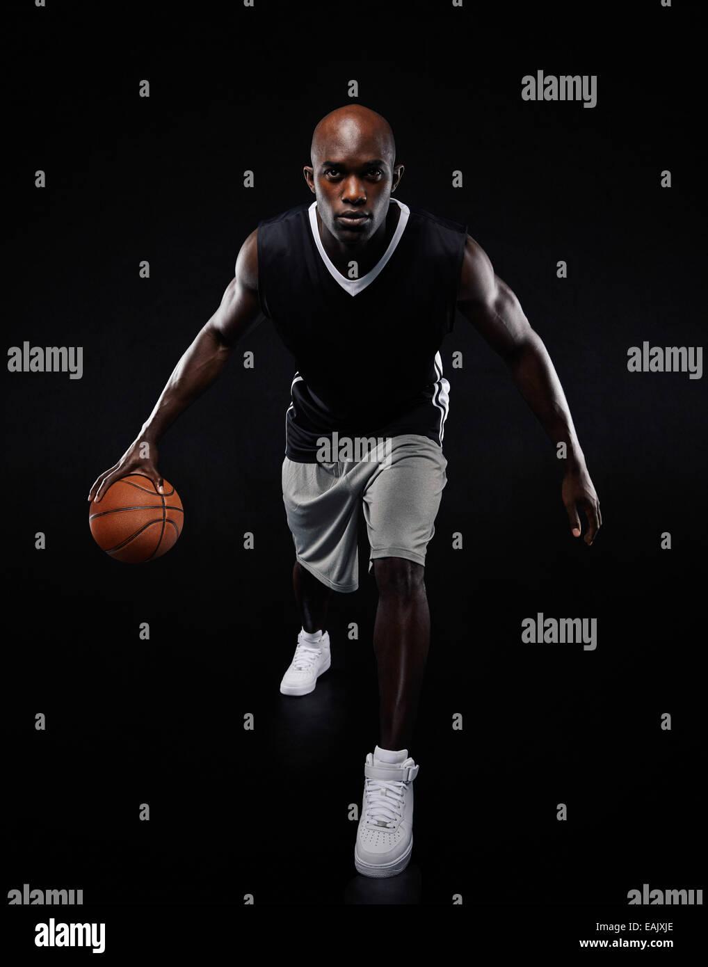 Longitud total retrato de joven jugador de baloncesto jugando sobre fondo negro. Colocar atleta masculino africano Imagen De Stock