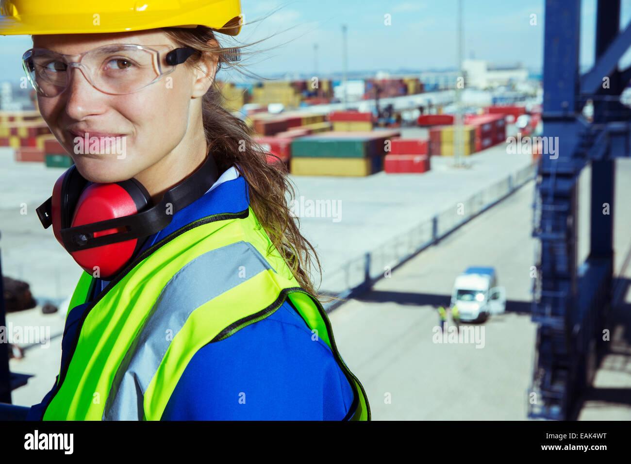 Trabajador sonriendo cerca de contenedores de carga Foto de stock