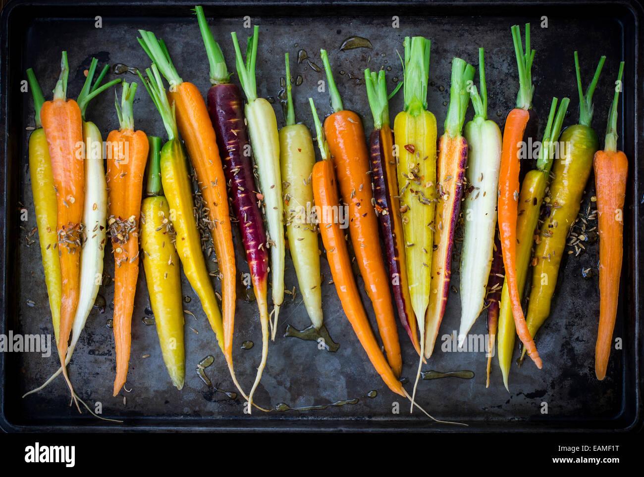 Rainbow zanahorias con aceite de oliva y especias sobre Dark Vintage Pan Imagen De Stock