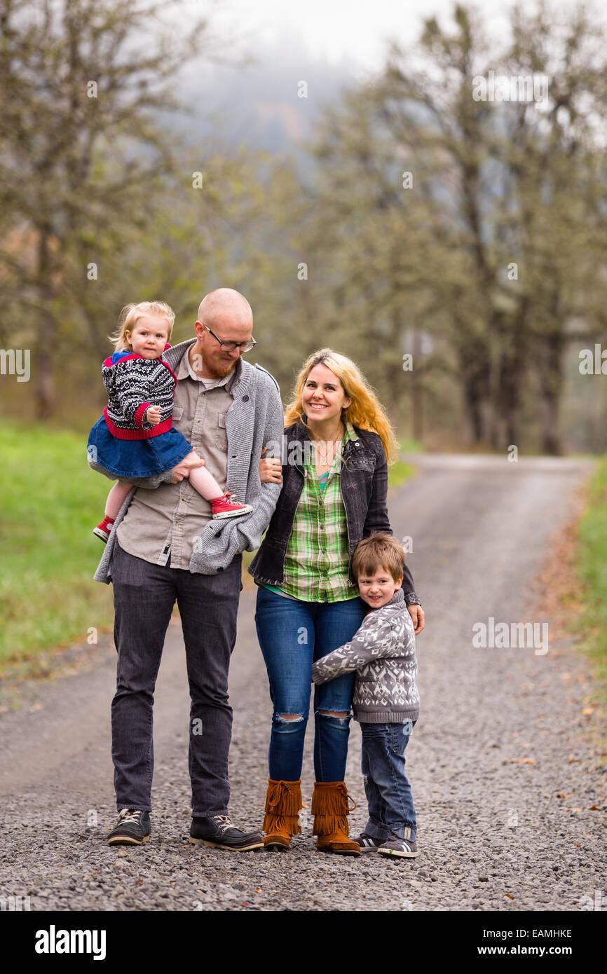Foto de familia de una madre, un padre y sus dos hijos, un niño y una niña afuera en el otoño. Imagen De Stock