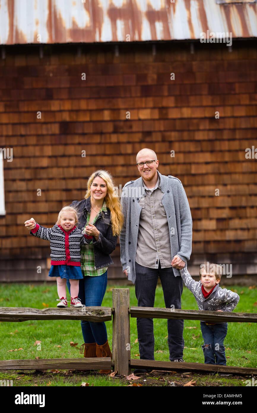 Estilo de vida familiar retrato de una madre, padre, hijo e hija en frente de un rústico granero en el país. Imagen De Stock