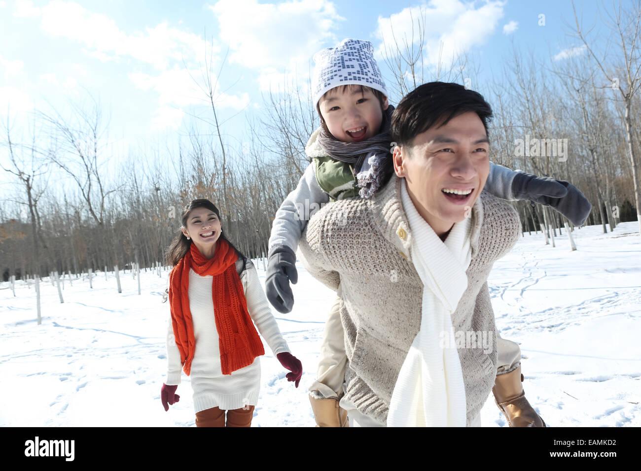 El padre y la madre con su hijo corriendo en la nieve. Imagen De Stock