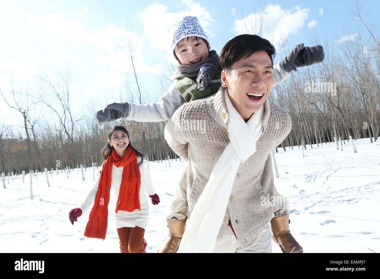 Una familia de tres corriendo en la nieve. Imagen De Stock