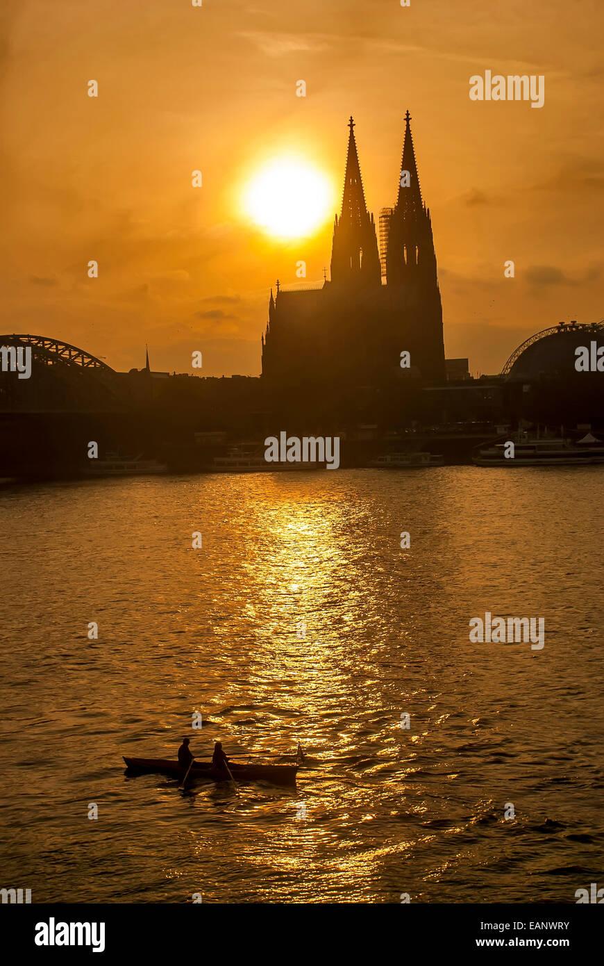 Duas pessoas passeando em un barco remo ningún río Reno assistindo o Pôr do Sol atrás da Catedral de Colonia. / Foto de stock