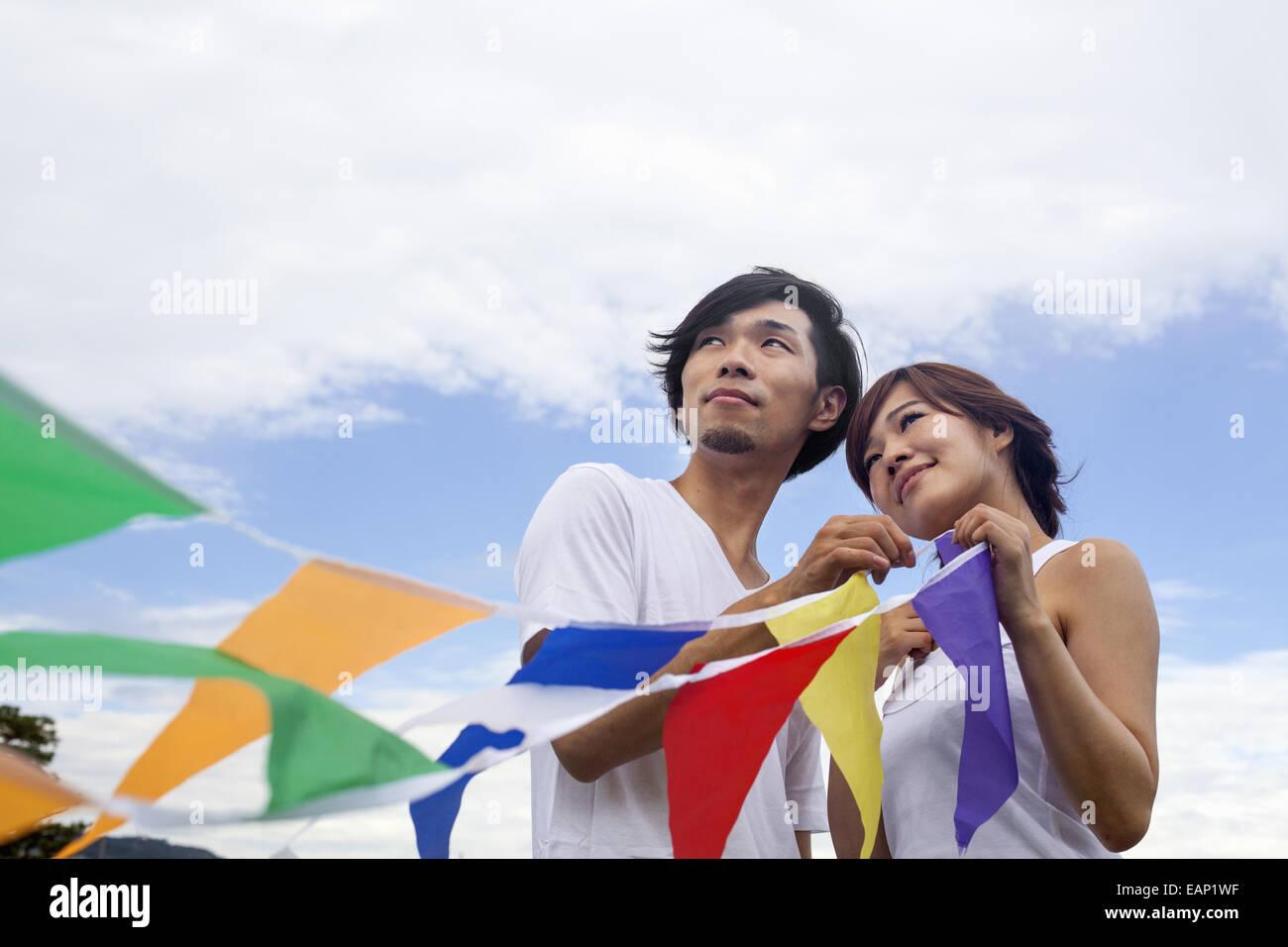Una pareja, un hombre y una mujer en un parque Kyoto sosteniendo una hilera de coloridas banderas. Imagen De Stock