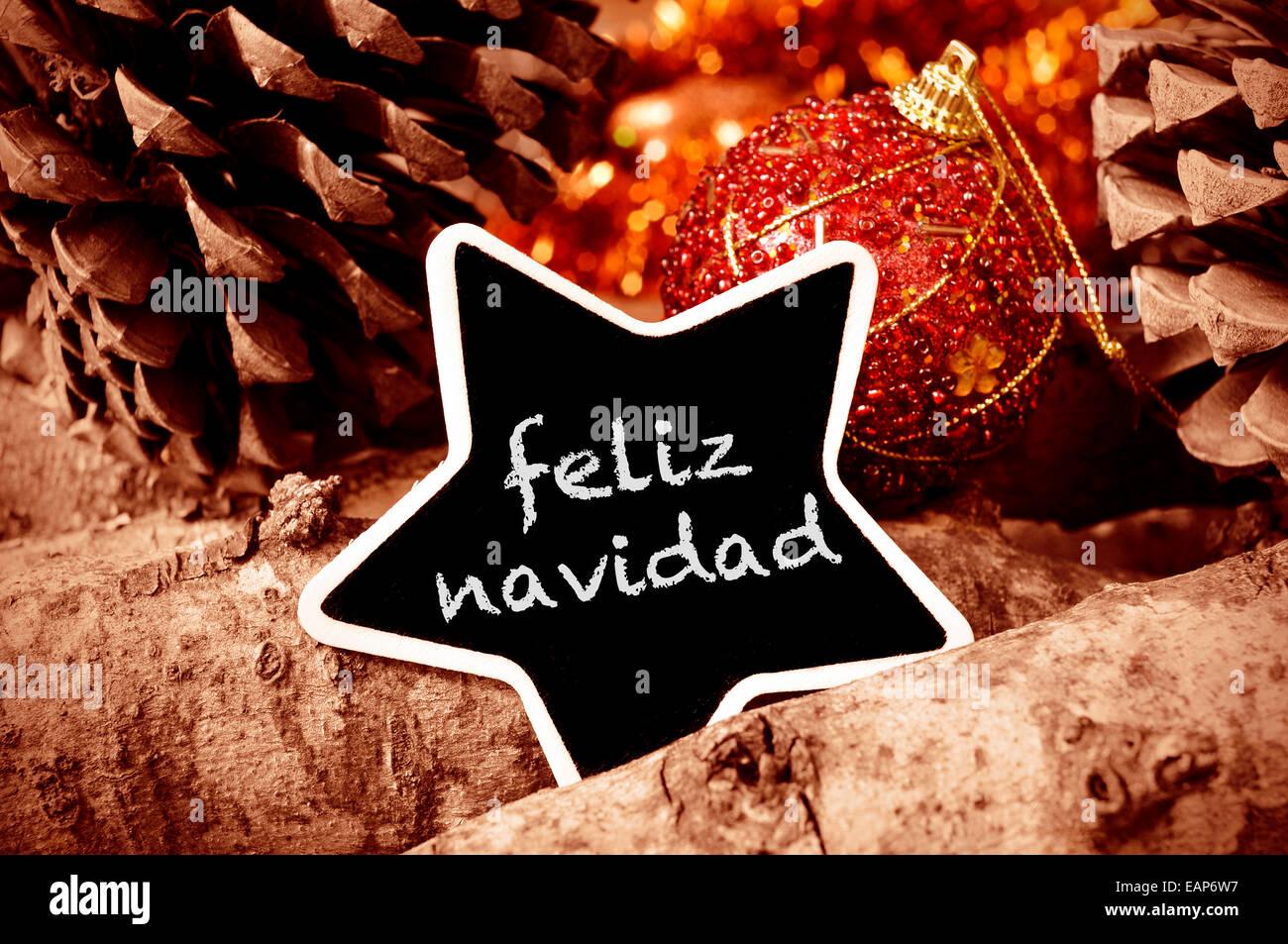 El texto feliz Navidad, Feliz Navidad escrito en español en una pizarra en forma de estrella, y algunos adornos Imagen De Stock