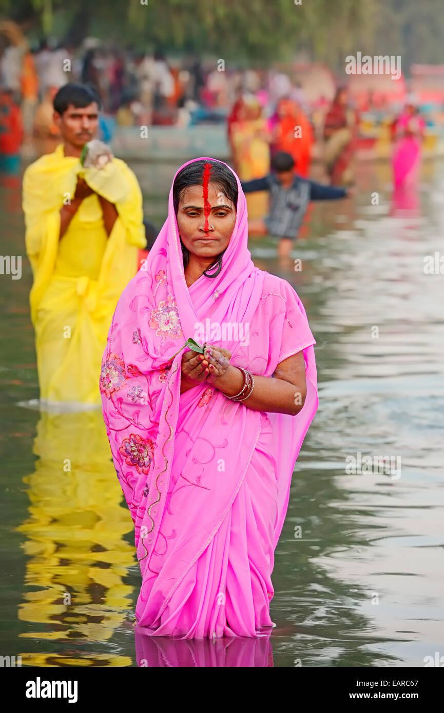 Hombre y mujer vistiendo un sari parado en agua durante el Festival ...