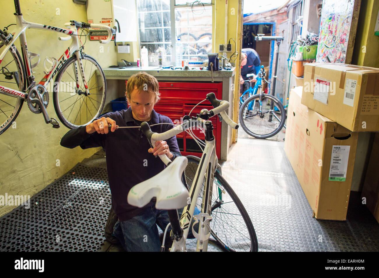 Un trabajador ajuste reparación arreglando bicicletas ciclos en la Cumbre, independiente pequeño centro Imagen De Stock