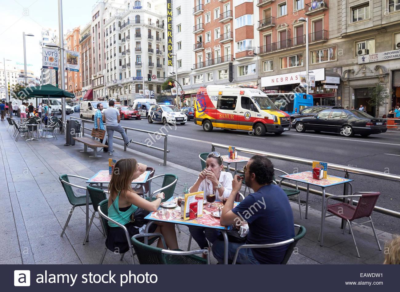 Personas sentadas en una mesa en una cafetería de la calle almorzando en Gran Via de Madrid en España Imagen De Stock