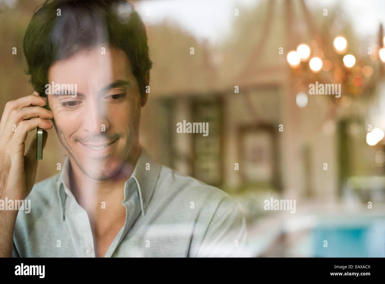 Hombre utilizando teléfono celular en casa Imagen De Stock