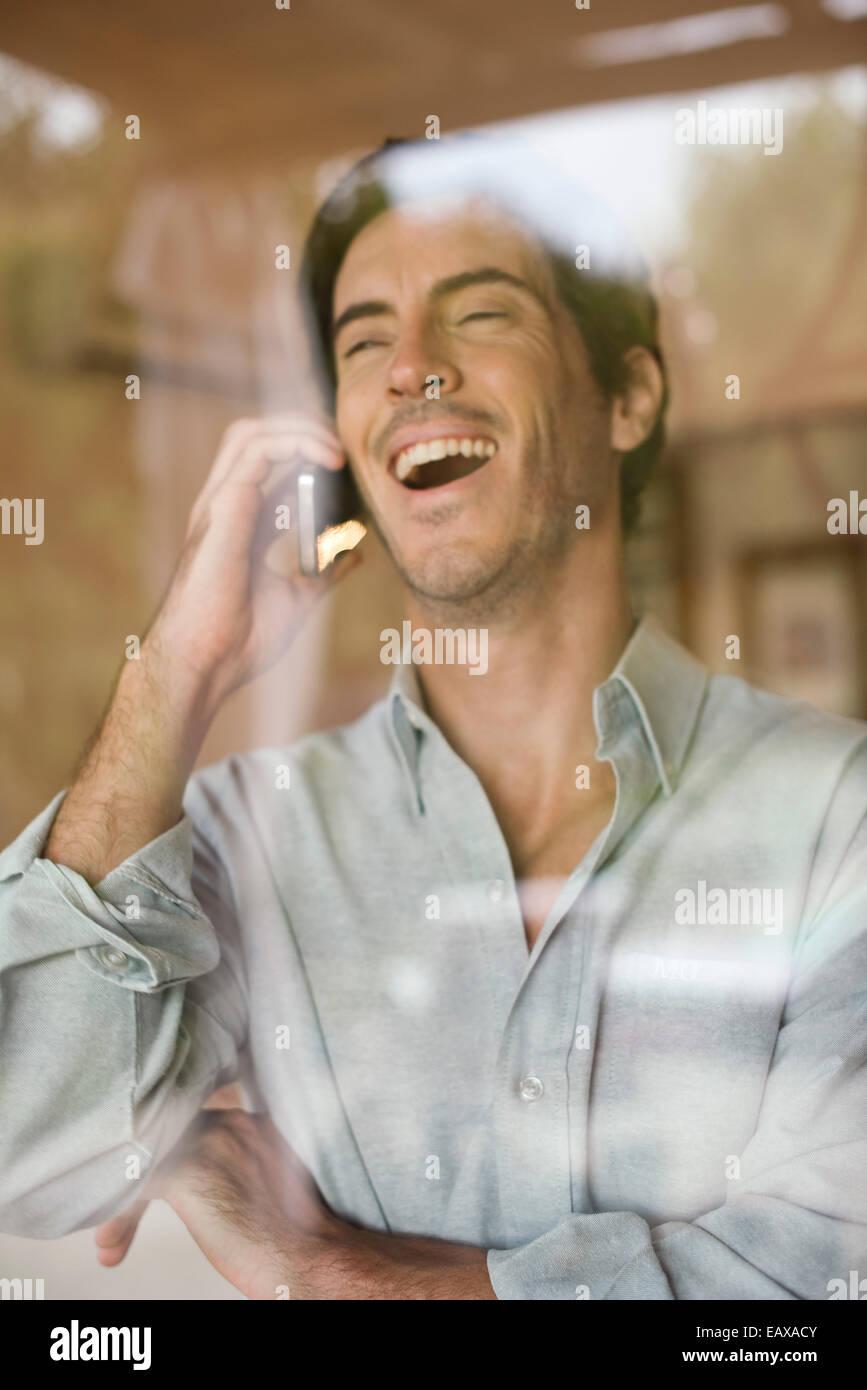 Hombre utilizando teléfono celular estallan riendo Imagen De Stock