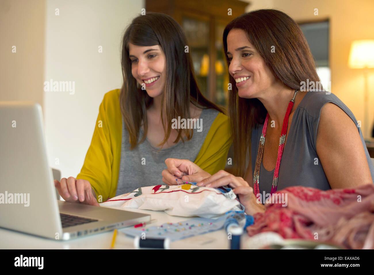 Hermanas bordado de aprendizaje juntos viendo vídeos online Foto de stock