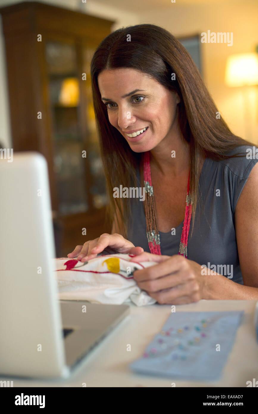 Mujer costura y utilizando equipo portátil Foto de stock