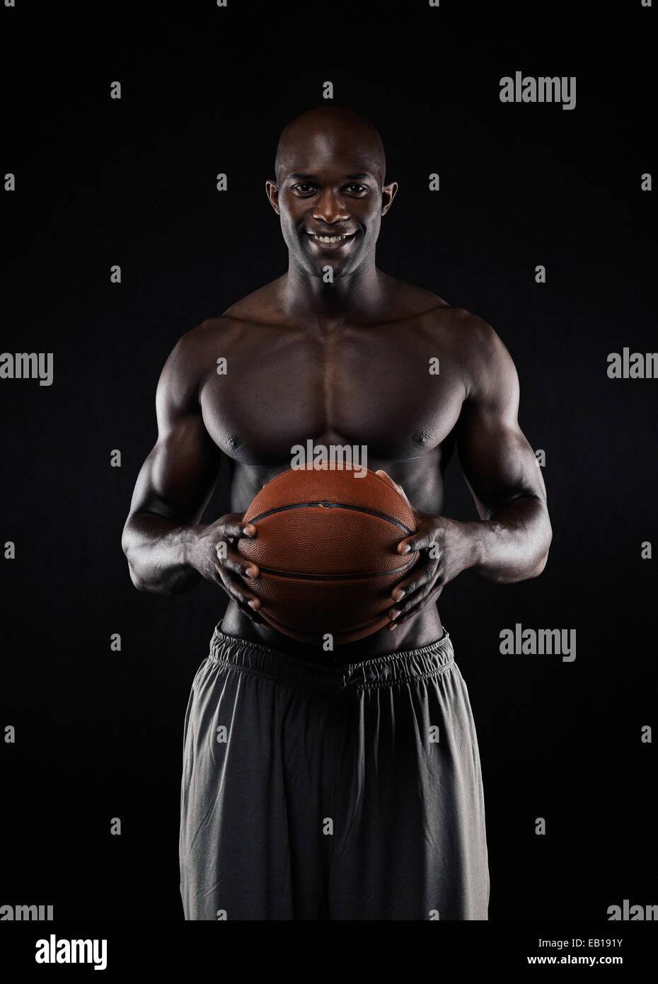 Foto de estudio de joven en pantalones cortos de baloncesto holding sonriendo ante la cámara. Colocar joven Imagen De Stock