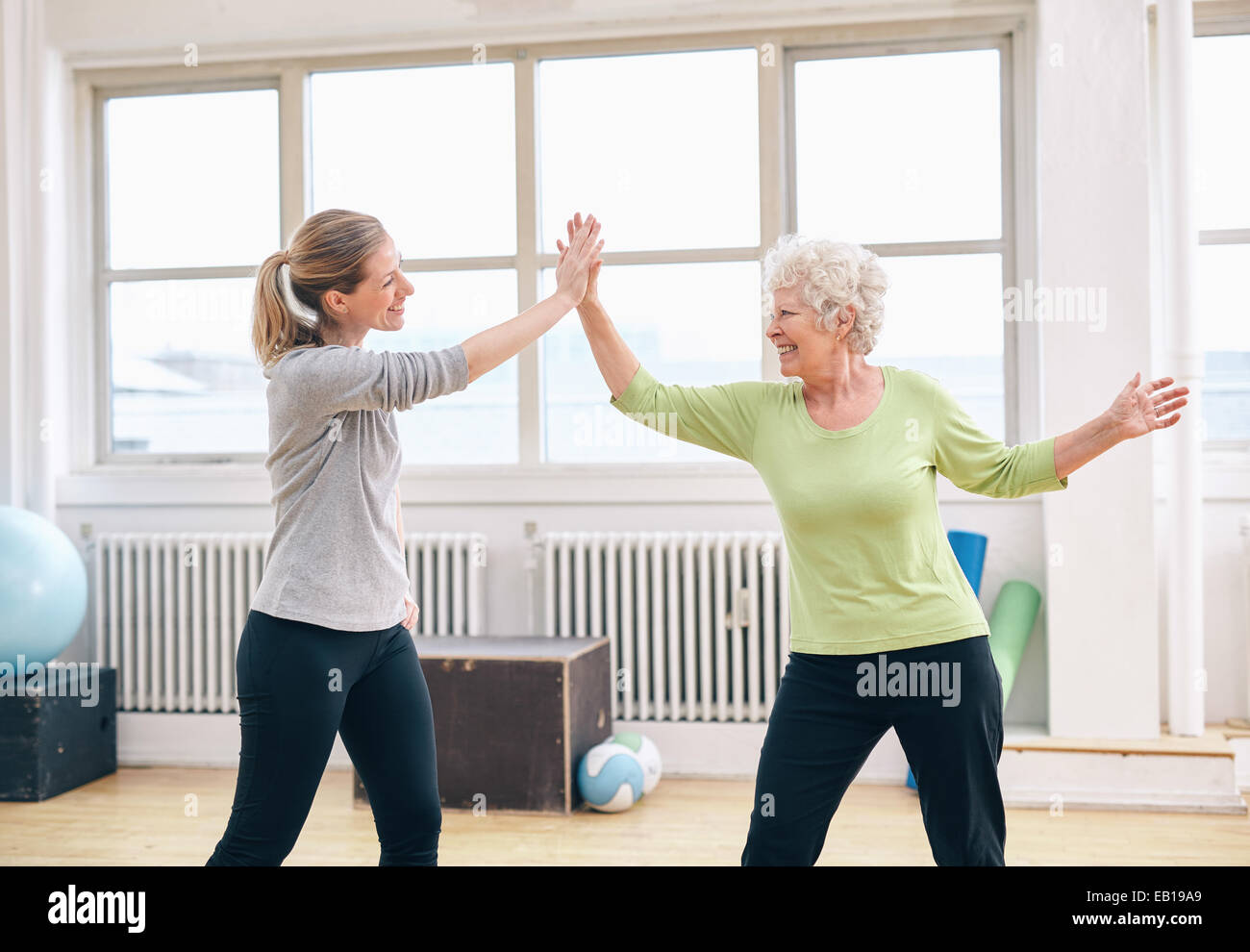 Mujer Senior High Five dando a su fisioterapeuta en rehab. Feliz anciana celebrando el éxito con su fitness instr Foto de stock