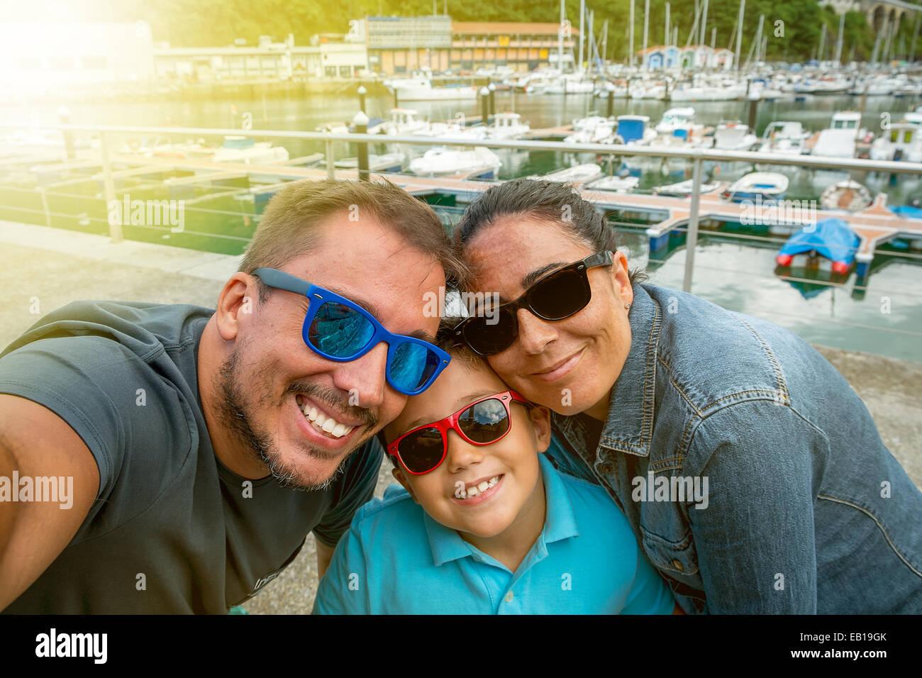 Familia divirtiéndose con gafas de sol y saludando a una cámara tomando selfie fotografía en vacaciones Imagen De Stock