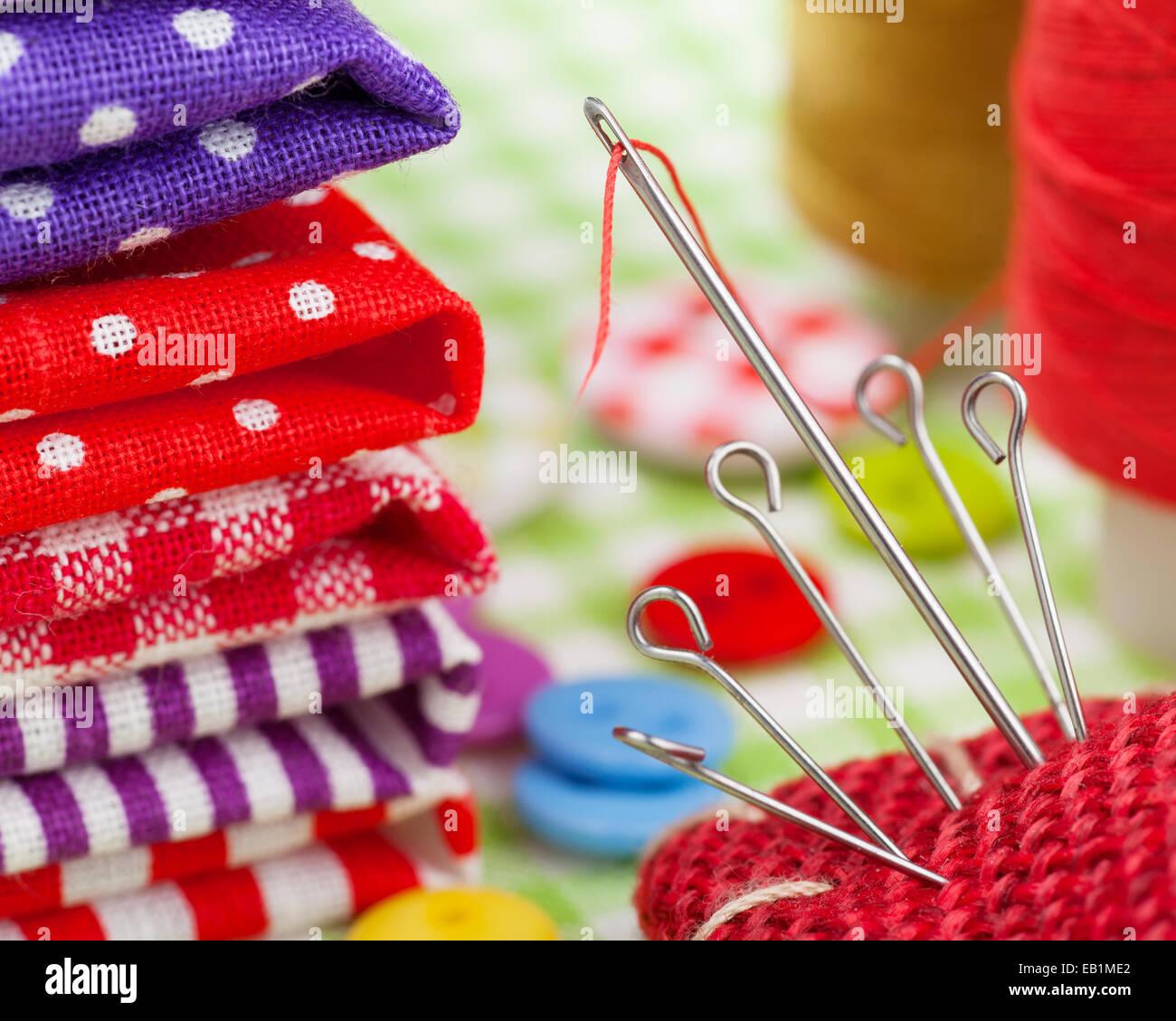 Elementos de costura: telas coloridas, botones acerico, dedal, bobina de hilo Foto de stock