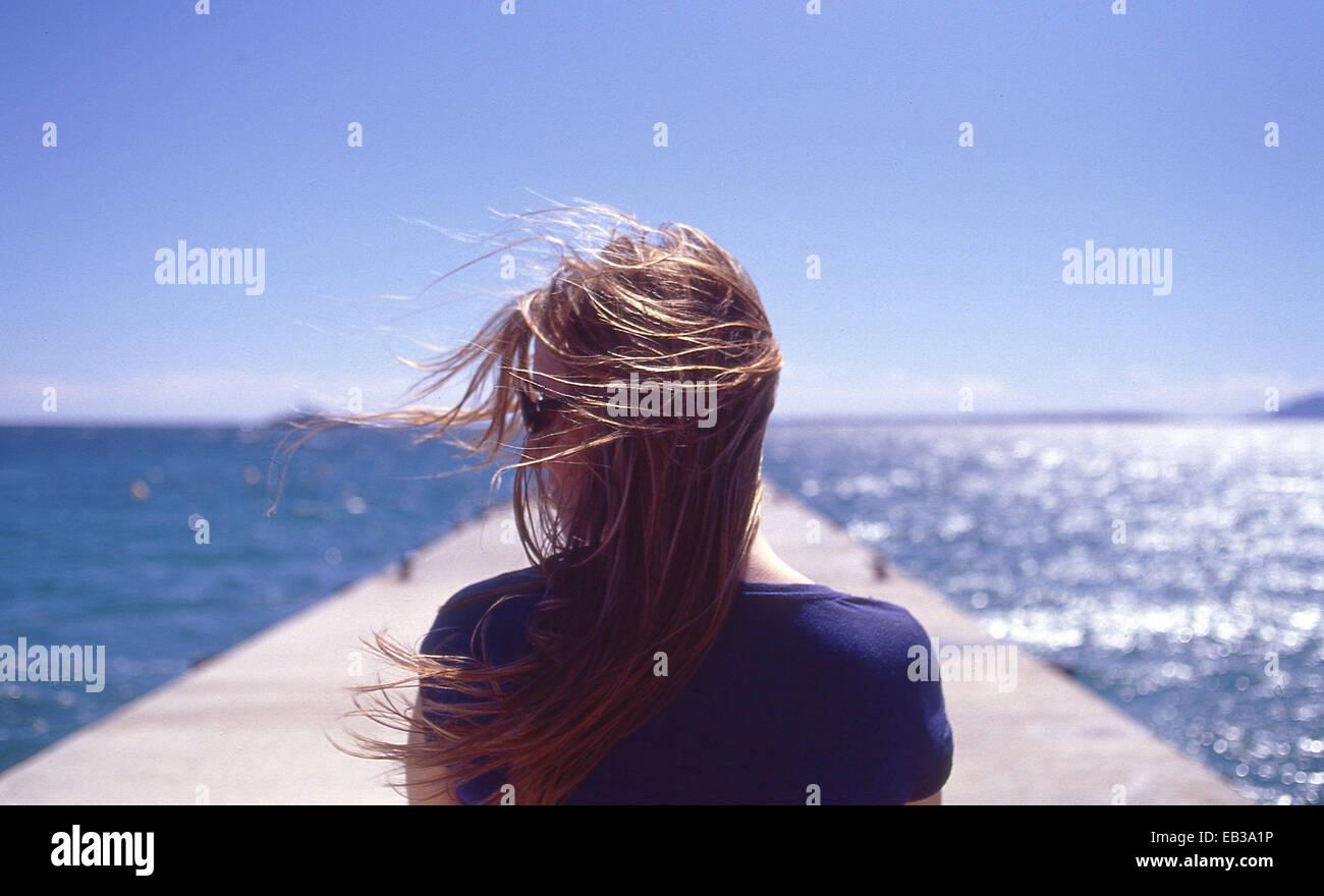 Francia, Juan les Pins, vista trasera de la mujer con el viento soplando Imagen De Stock