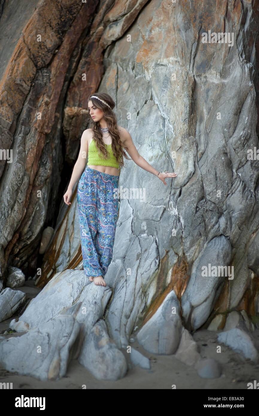 Mujer joven de pie sobre las rocas en la playa Imagen De Stock