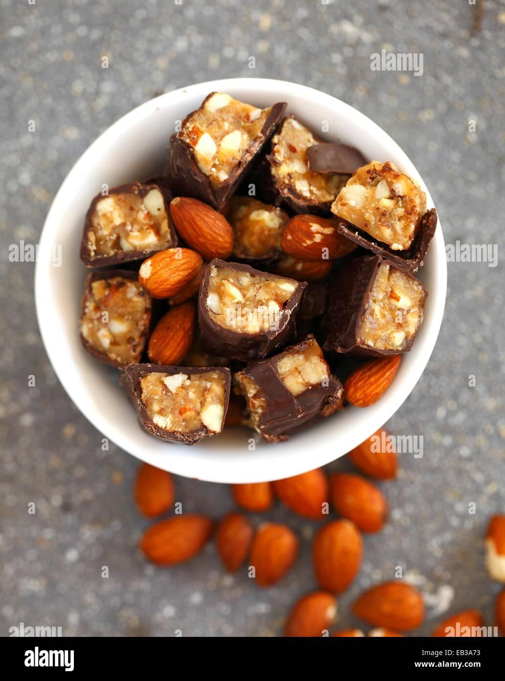Barras de caramelo de chocolate cortado en trozos mezclado con almendras enteras en el tazón de porcelana blanca Imagen De Stock