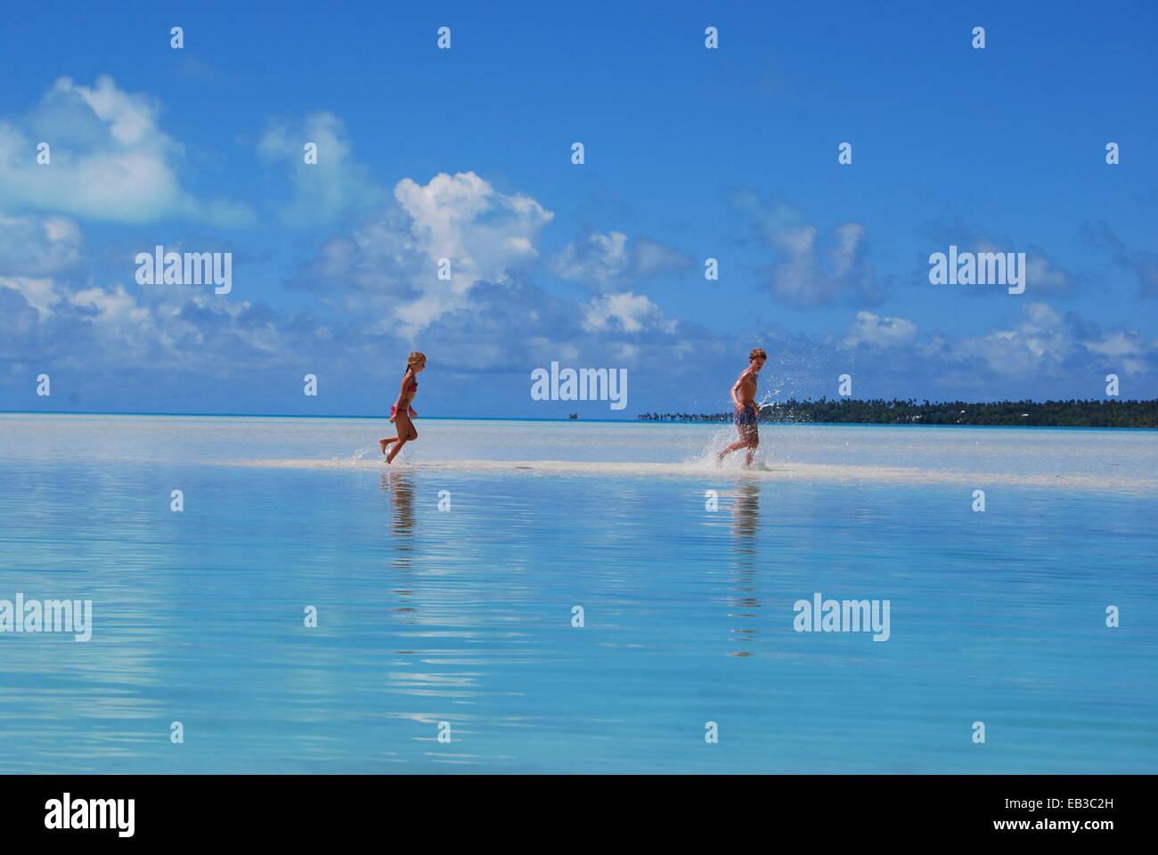 Islas Cook, dos niños (8-9, 10-11) que se ejecutan en el mar Imagen De Stock