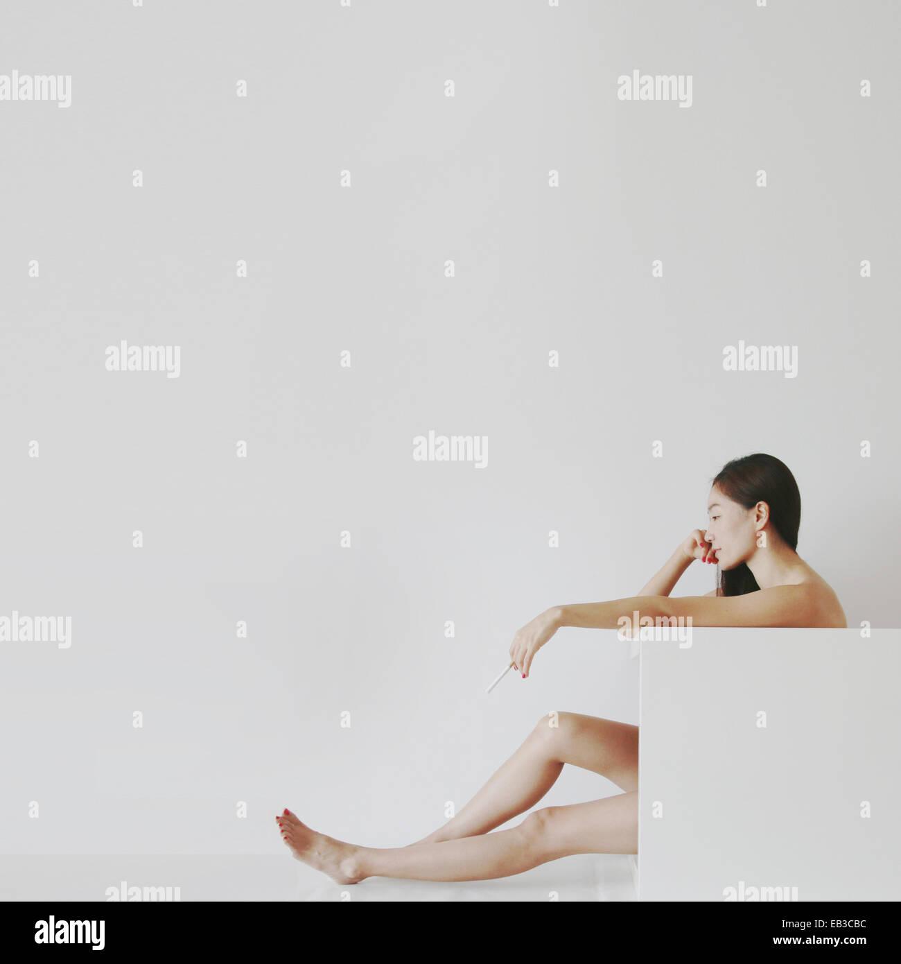 China, Hong Kong, hermosa mujer sosteniendo cigarrillo Imagen De Stock