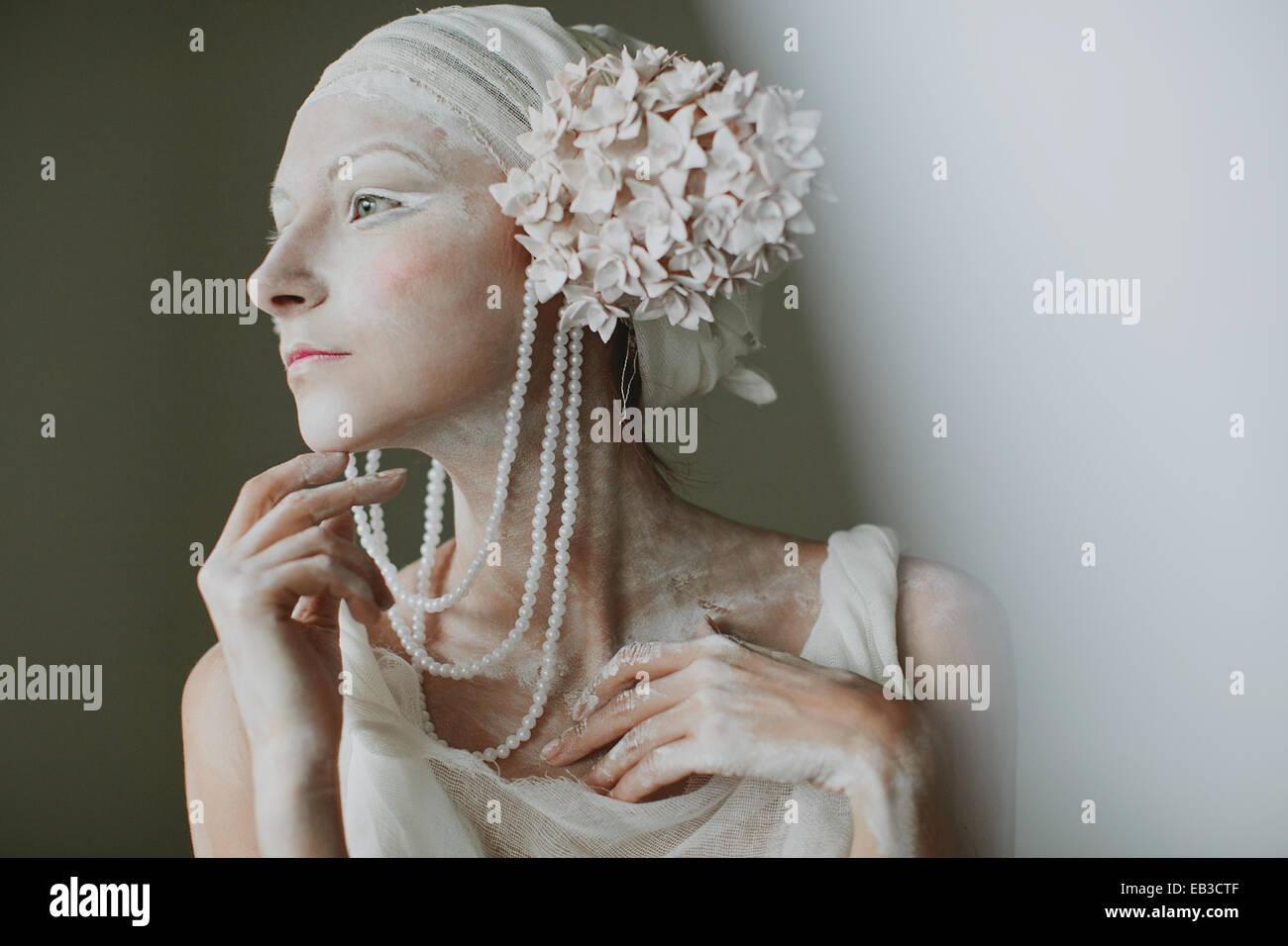 Retrato de joven mujer vistiendo, greasepaint, abalorios y adornos de oreja semejando inflorescencia Foto de stock
