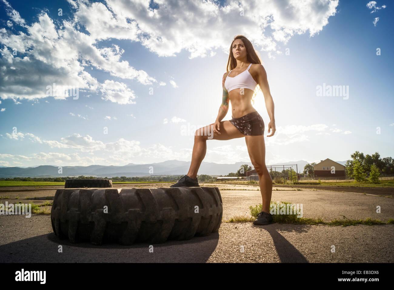 Ee.Uu., Colorado, Condado de Jefferson, Arvada, atleta femenina posando con neumáticos de pista Imagen De Stock