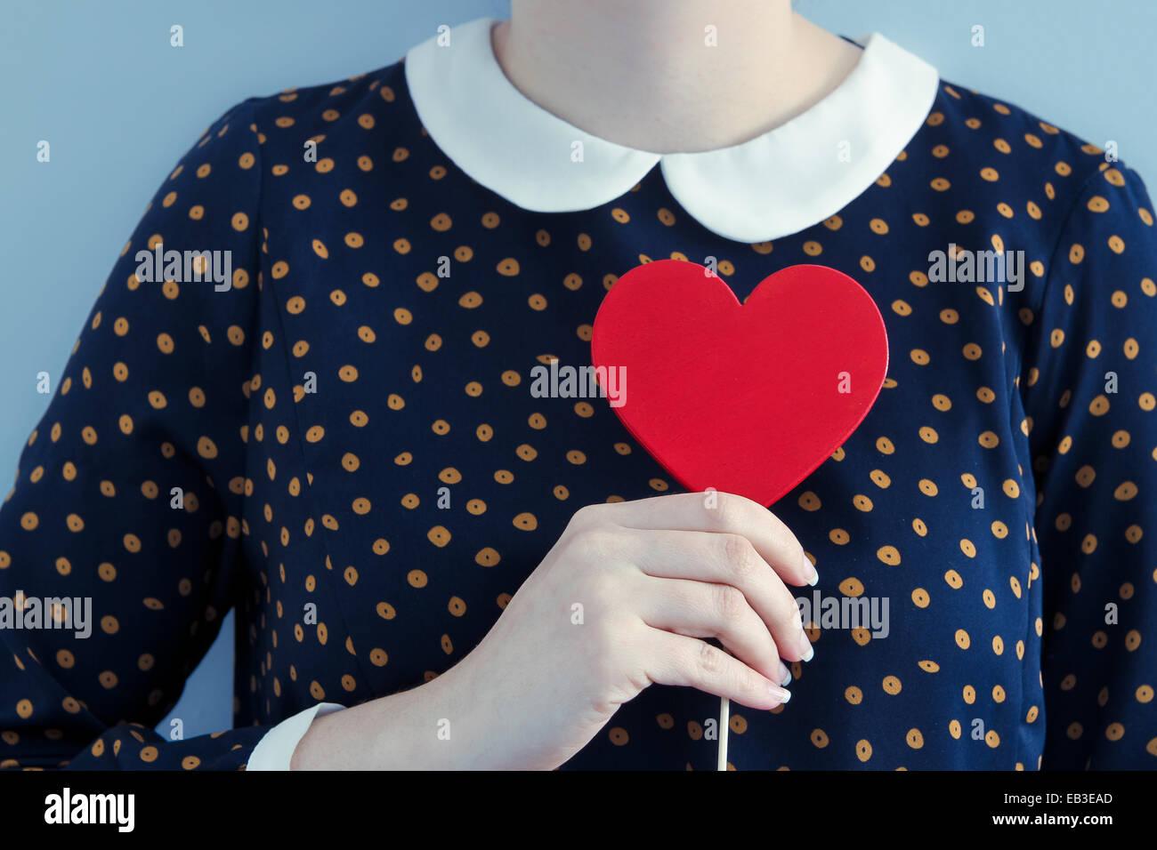 Mujer vistiendo traje de lunares sosteniendo objetos con forma de corazón Imagen De Stock