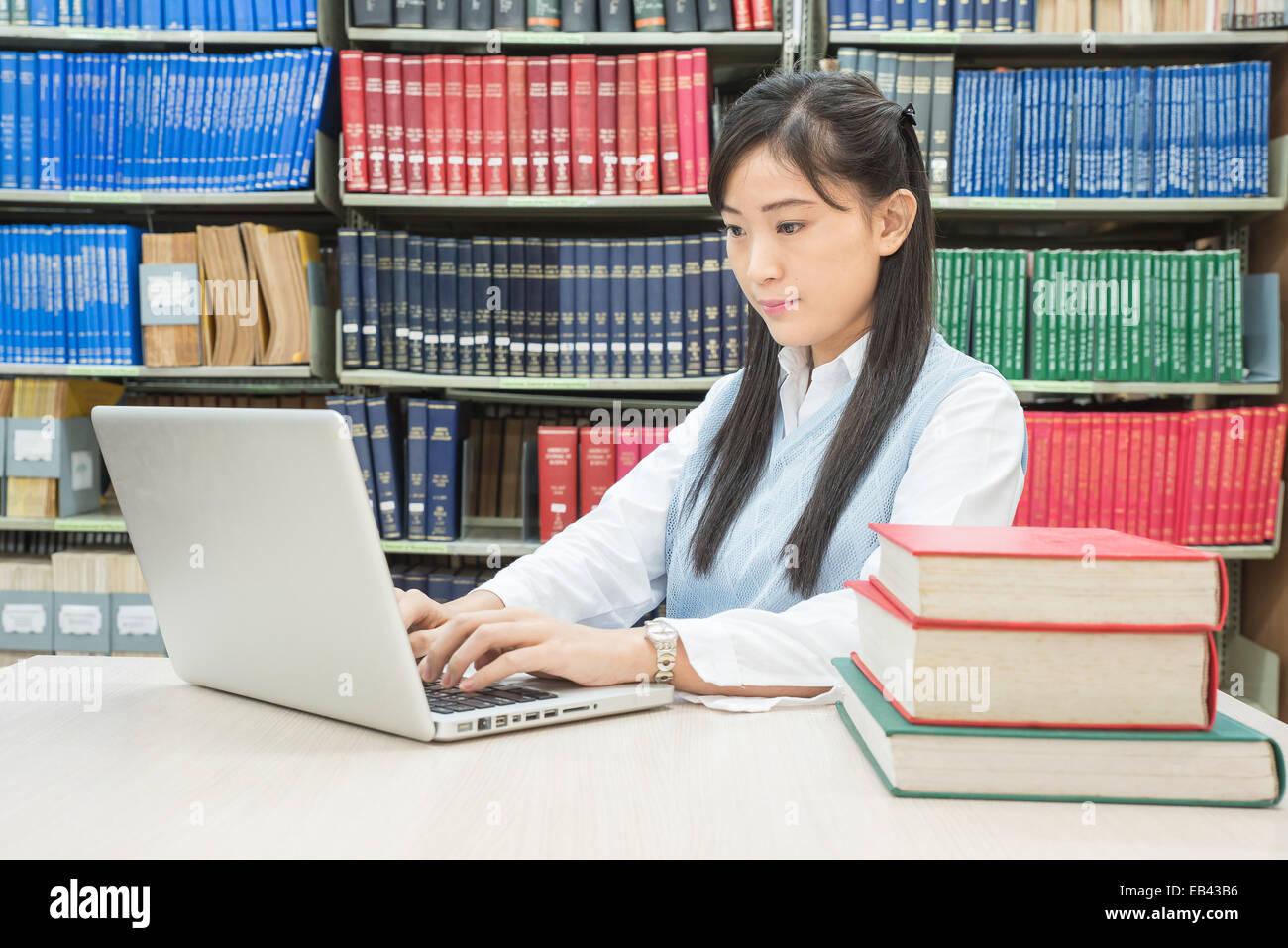 Estudiante asiático escribiendo en el portátil en la biblioteca Foto de stock